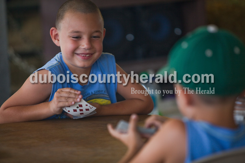 Will Hasenour of Ferdinand, 6, played cards with his twin brother, Charlie, in the cattle barn at the Dubois County 4-H Fairgrounds on Sunday. Rachel Mummey/The Herald