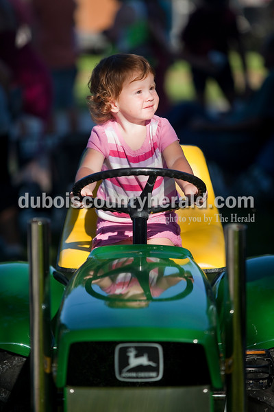 Isabelle Riley of Eckerty, 1, pretended to drive the tractor for the adult tractor pull at Haysville Park during the  51st annual Haysville Sommerfest on Friday. Rachel Mummey/The Herald