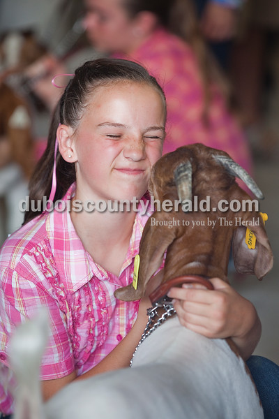 Grace Sickbert of Huntingburg, 11, nuzzled close to her goat named Finn before the start of the Intermediate Showmanship Goat Show at the Dubois County 4-H Fairgrounds on Sunday. Rachel Mummey/The Herald