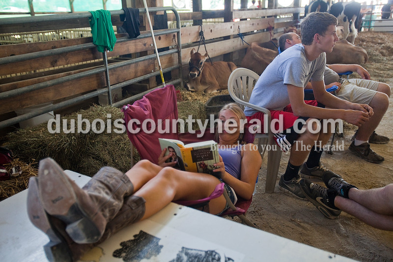 Rachel Mummey/The Herald<br /> Sabrina Ferguson of Huntingburg, 18, read a book while passing time with Logan Steckler of St. Henry, 17, in the cattle barn at the Dubois County 4-H Fair on Sunday. Rachel Mummey/The Herald