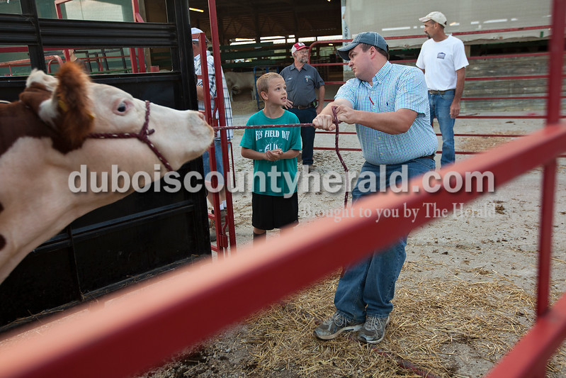 Calvin Hasenour of Ferdinand, 9, left, received help from his uncle Seth Leinenbach of Cincinnati, Ohio, unloading Calvin's steer named Junior as they checked him into the Dubois County 4-H Fair on Saturday morning at the fairgrounds. This is the first year that Calvin is showing at the fair. Leinenbach is a Jasper native. Dave Weatherwax/The Herald