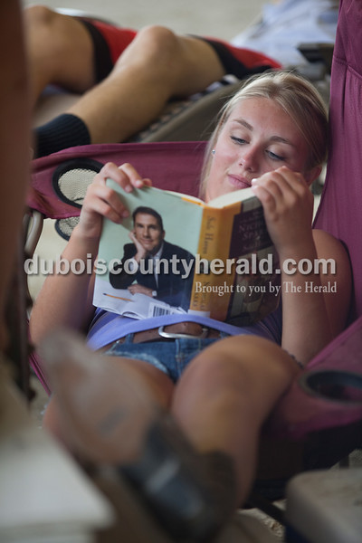Sabrina Ferguson of Huntingburg, 18, read a book while lounging in the cattle barn at the Dubois County 4-H Fairgrounds on Sunday. Rachel Mummey/The Herald
