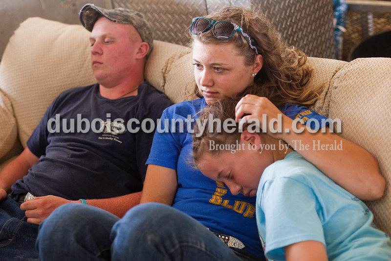 Greg Kreinein of Jasper, 17, left,  Madi Giesler of Ferdinand, 15, and Hannah Schwenk of Jasper, 10, rested on a couch in the cattle barn during the Dubois County 4-H Fair on Sunday. Rachel Mummey/The Herald