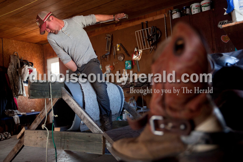 """Most evenings, Travis Leistner spends a few minutes atop a barrel covered with a carpet in the garage of his Holland home, as he did the evening of March 12. On the barrel, he practices the maneuvers he uses to counter the movement of a bull. """"It's like a dancing partner. You want to keep in perfect timing and rhythm,"""" he said. The 23-year-old rode his first bull in December 2011 in New Caney, Texas. Since then, he has ridden about 160 bulls. Dave Weatherwax/The Herald"""
