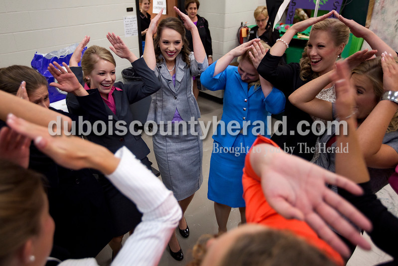 Miss Strassenfest contestants Kendra Kern, 20, left, Mallory Humbert, 19, Hayley Hildenbrand, 19, Kimberly Gootee, 20, and Samantha Erny, 19, all of Jasper, made the shape of a tiara above their heads as they broke from a group huddle before the start of the pageant at Jasper Middle School on Saturday. Dave Weatherwax/The Herald