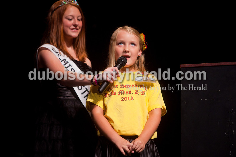 2012 Junior Miss Strassenfest Ashley Whitsitt of Jasper, 13, held the microphone for Little Miss Strassenfest contestant Grace Jarboe of Jasper, 8,  to answer her interview questions during the contest Saturday afternoon in the Jasper Middle School auditorium. Dave Weatherwax/The Herald