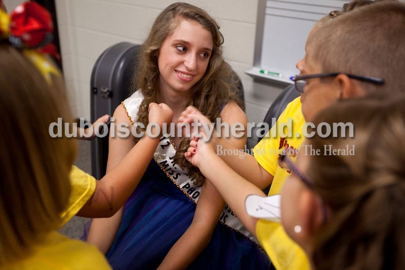 2012 Junior Miss Strassenfest Miss Photogenic Priscilla Olson of Jasper, 14, was surrounded by 2013 Little Miss and Mister contestants as they pretended to hold microphones and ask her several questions as the contestants waited on the judges to select a winner Saturday afternoon at Jasper Middle School.  Dave Weatherwax/The Herald