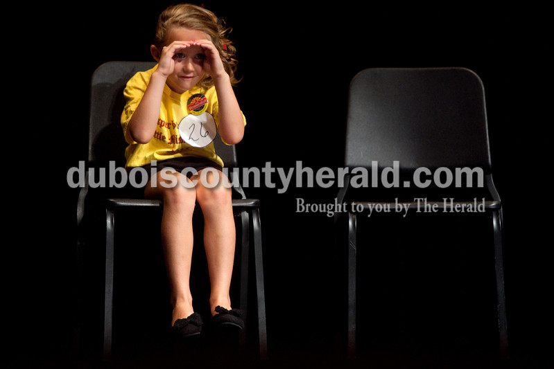 Little Miss Strassenfest contestant Jillian Mueller of Jasper, 7, shielded her eyes from the stage lights to get a glimpse into the crowd during the contest Saturday afternoon in the Jasper Middle School auditorium.  Dave Weatherwax/The Herald