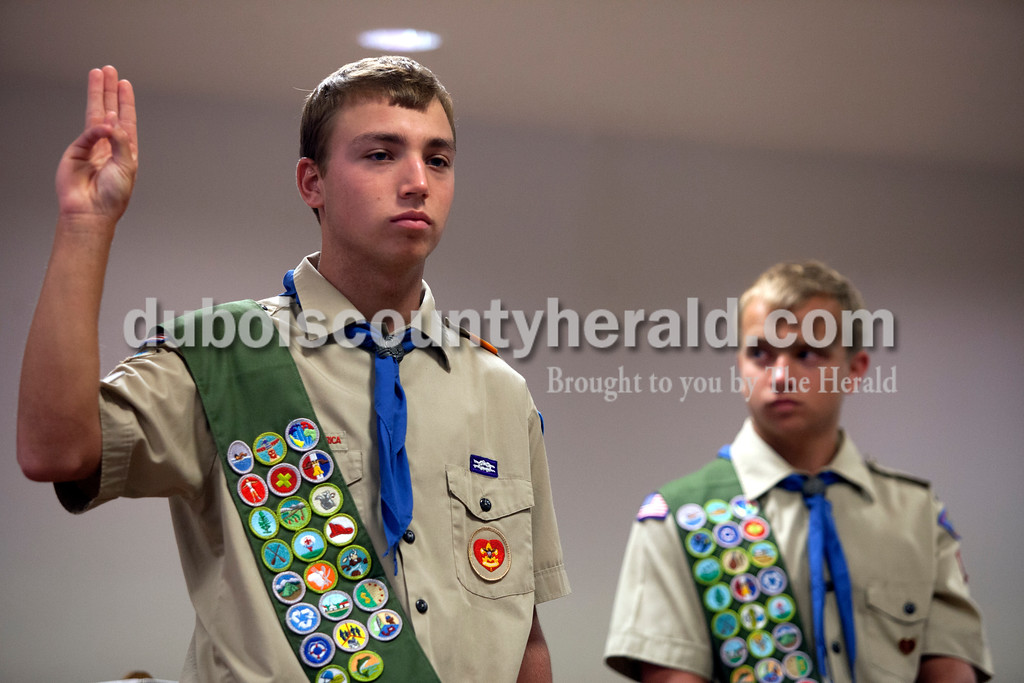 Ariana van den Akker/The Herald<br /> Eli Seng of Jasper, 18, took his Eagle charge while his twin brother Ben waited to take his during their Eagle Scout pinning ceremony at the Arnold F. Habig Community Center on Sunday.  This year, Ben and Eli joined their two older brothers Heath and Jeff in becoming Eagle Scouts.