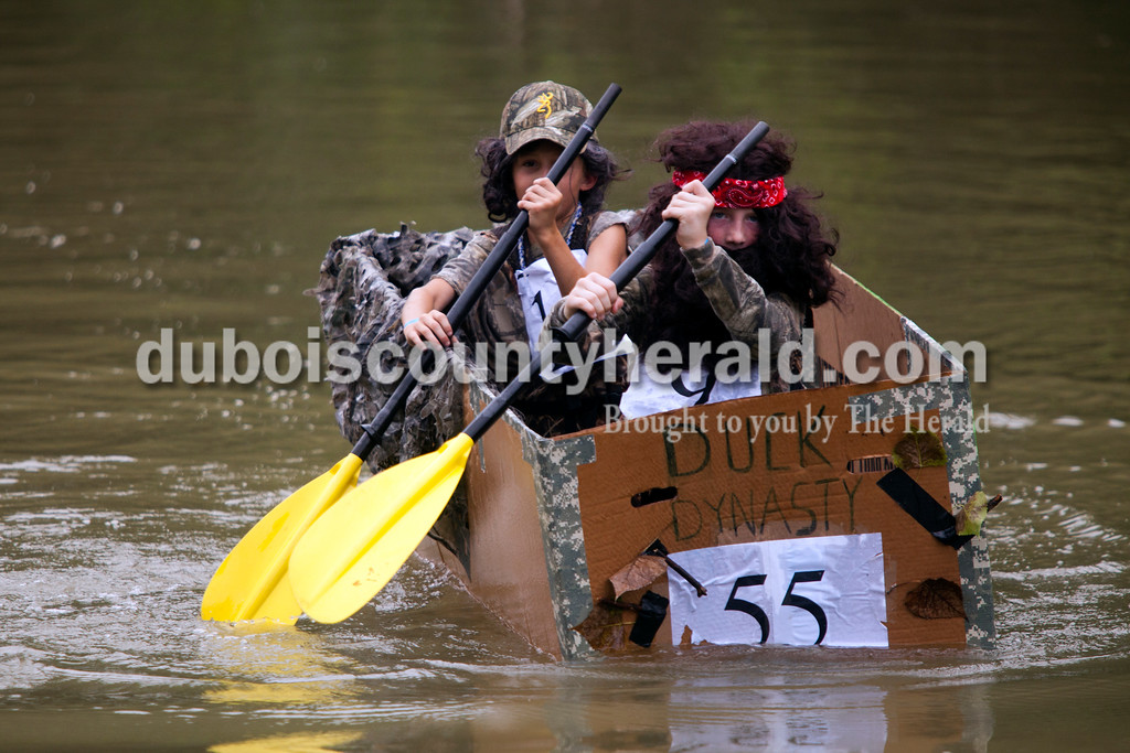 """Ariana van den Akker/The Herald<br /> Luke Hassenour, 9, and Will Weinzapfel, 10, both of St. Anthony, rowed their Duck Dynasty-themed coffin-style boat to victory during the """"hoot race"""" during the Holy Family School Cardboard Boat Regatta in Jasper on Saturday."""