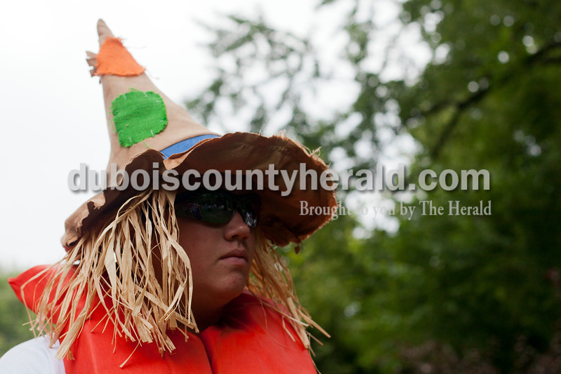 Ariana van den Akker/The Herald<br /> Luke Taylor of Huntingburg paused in his scarecrow costume before the Holy Family SchoolCardboard Boat Regatta in the Patoka River in Jasper on Saturday.  Taylor was on the Home Instead corporate boat that was Wizard of Oz-themed and shaped like a ruby slipper.