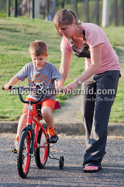 "Rachel Mummey/The Herald<br /> Reece Harder of Jasper, 5, received a little help from his mom, Racheal, while practicing riding his new bicycle at Gutzweiler Park in Jasper on Tuesday. In addition to the new bike, Reece began attending kindergarten at Fifth Street Elementary School this week too. ""It's been a big week for him so far,"" Rachael said."