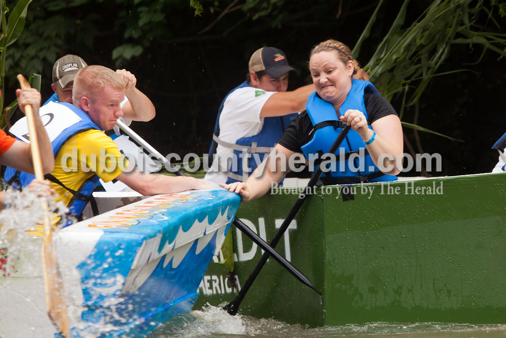 Ariana van den Akker/The Herald<br /> Leslie Petry of Holland in the Farm Credit boat and Brendan Perkins in the Herald boat pushed each other's boats away after the Herald boat started turning around during the Holy Family SchoolCardboard Boat Regatta in the Patoka River in Jasper on Saturday.
