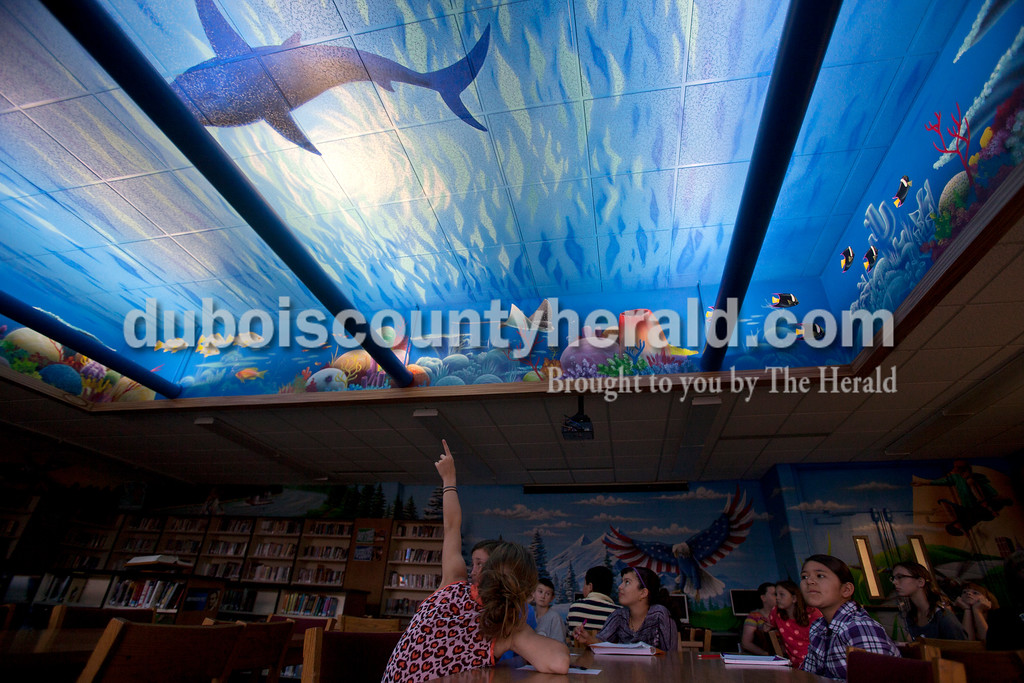 Ariana van den Akker/The Herald<br /> Kolby Jones of Huntingburg, 11, pointed to a silhouette of a shark painted on the library ceiling on Friday at Southridge Middle School.  The school commissioned the mural, which covers the ceiling and the walls, from Orange Moon Art Studio, comprised of Michael and Amanda Smith.