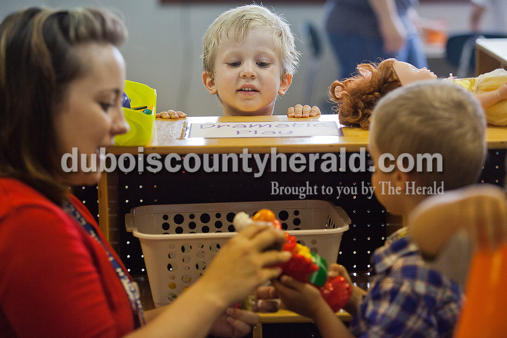 Rachel Mummey/The Herald<br /> Lincoln Trail Elementary School preschooler Griffin Haas, 3, center, peaked over to watch classmate Kohen Paulin, 3, left, and teacher Casey Guthrie, right, play with an Elmo doll during their first day of school in Lamar on Monday. This is the first year a preschool program has been offered at Lincoln Trail Elementary School.