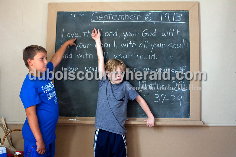 """Ariana van den Akker/The Herald<br /> Grant Schepers, a fourth-grader at Celestine Elementary, and Keegan Twitty, a fourth-grader at North Knox Intermediate School in Bruceville, pointed out the date and bible verse of the day while on a field trip to the White River Valley Antique show in Elnora on Friday.  The antique show featured a village meant to take visitors back a hundred years to learn about what life was like back then.  Part of that village included a one-room school where Donna Heshelman of Brownsburg, or """"Miss Ella"""" the school marm as she is known for the week, demonstrated what class would have been like in 1913."""