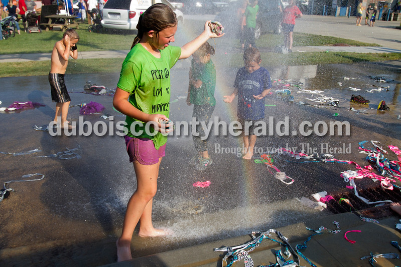 Gracee Sullivan of Lynnville, 11, washed off in the shower from a firehouse after the hog wrestling competition at the Dale Fall Fest on Saturday. Ariana van den Akker/The Herald
