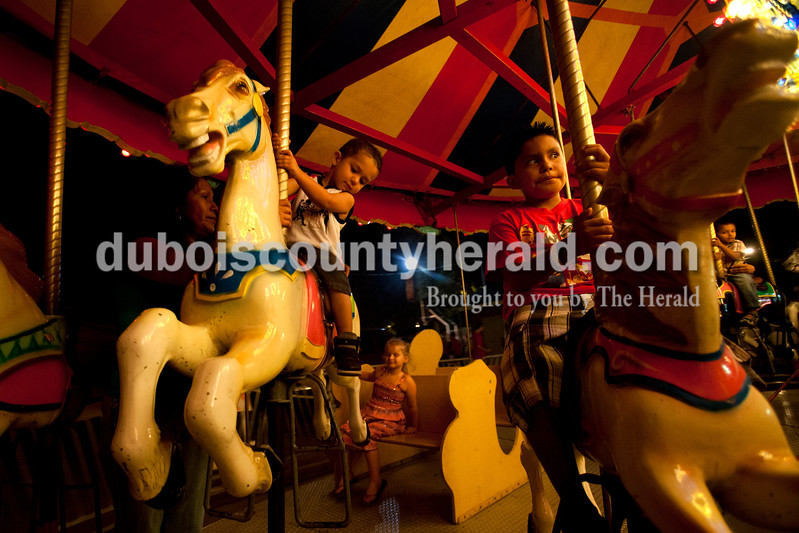 Delia Ramierez of Huntingburg, left, rode the carrousel with her two children Serefin, 3, and Jose, 8, at the Dale Fall Fest on Saturday. Ariana van den Akker/The Herald
