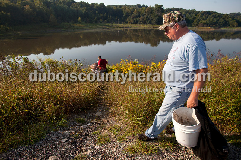 Ariana van den Akker/The Herald<br /> Ric Flick of of Wycliff walked to the water to clean up while Jerry Allstott of Birdseye looked for trash near the South Lick Fork Ramp at Patoka Lake Saturday morning.  Volunteers cleaned up trash at several of the ramps on the lake and then attended a free fish fry at Hoosier Hills Marina.