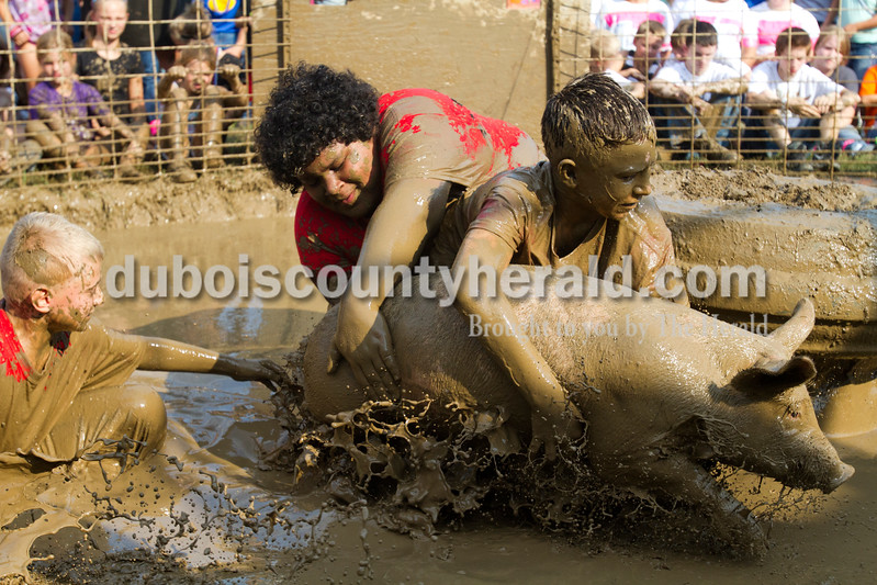 Koby Cassette of Dale, 10, left, fell in the mud while Dameion Bell of Gentryville, 10, and Zach Davis of Ferdinand, 11, tried to get their pig onto the tire during the hog wrestling competition  at the Dale Fall Fest on Saturday. Ariana van den Akker/The Herald