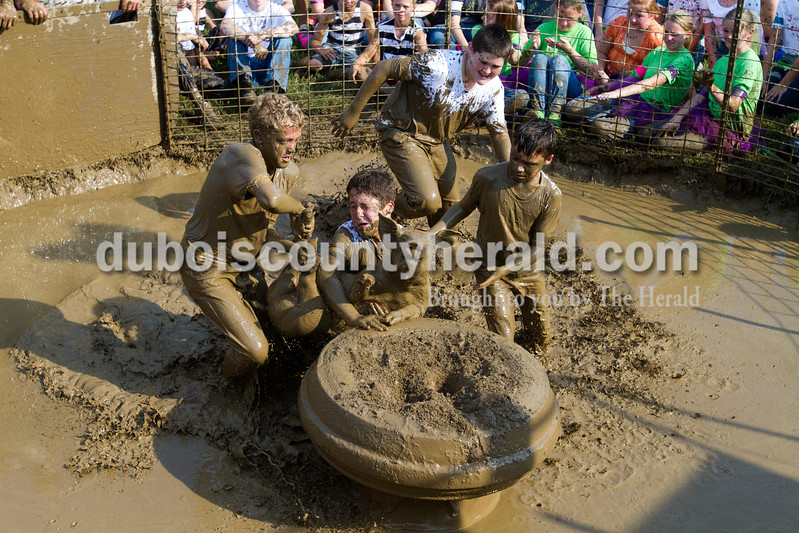 Cody Frakes of Santa Claus, 12, left, Phoenix Rodgers of Lamar, 11, Isaac Maddox of Santa Claus, 12, and Beau Heeke of Lamar, 12, tried to lift a hog onto the tire during the hog wresting competition at the Dale Fall Fest on Saturday.  They dropped the hog on the attempt and time ran out before they were able to finish. Ariana van den Akker/The Herald