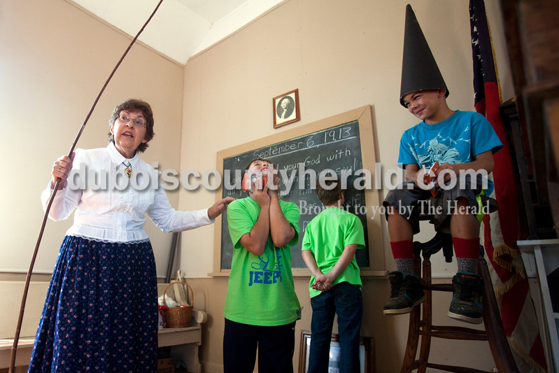 """Ariana van den Akker/The Herald<br /> Donna Heshelman of Brownsburg, who was pretending to be school marm """"Miss Ella,"""" in a one-room classroom set in 1913, explained to the class that Lane Jones, a fourth-grader at Dubois Elementary, who was talking during the lecture, would have to be smacked with a stick as a punishment while his classmate Seth Eckert, who was also talking, had to put his nose against the board and Andrew Gibbs, a third-grader at Bloomfield Elementary, sat on a stool wearing the dunce cap as his punishment while on a field trip to the White River Valley Antique show in Elnora on Friday.  The antique show also featured a village meant to take visitors back a hundred years to learn about what life was like back then, including what typical punishments were in a classroom."""