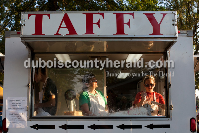 Peggy Politano of Evansville, left, and Ginger Coultas of Chrisney cut and wrapped up taffy to sell at the Dale Fall Fest on Saturday. Ariana van den Akker/The Herald
