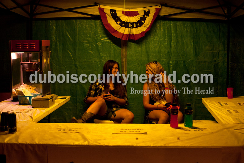 Brie Geiger of St. Meinrad, 17, left, and her sister Lexi, 15, shared a laugh while volunteering at the Dale Parks and Recreation booth at the Dale Fall Fest on Saturday. Ariana van den Akker/The Herald