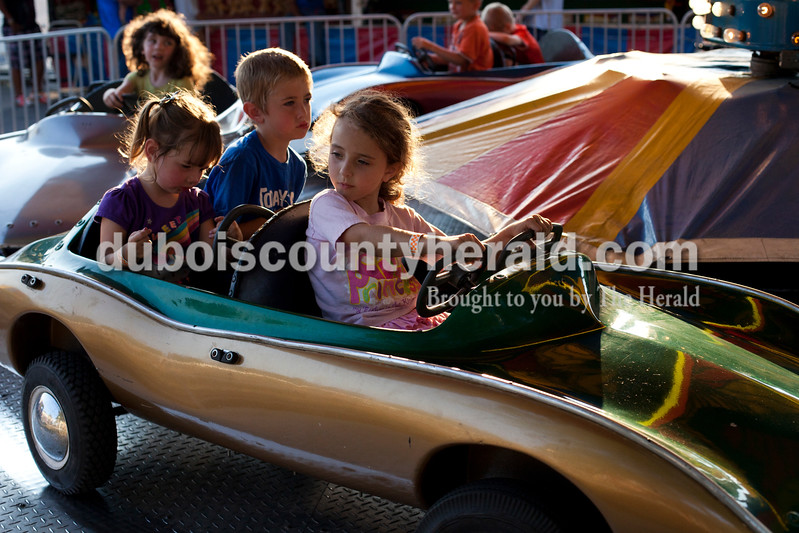 Kaylee Hart of Gentryville, 2, left, her brother Jacob, 5, and Alicia Fortune of Santa Claus, 5, rode a car ride at the Dale Fall Fest on Saturday. Ariana van den Akker/The Herald