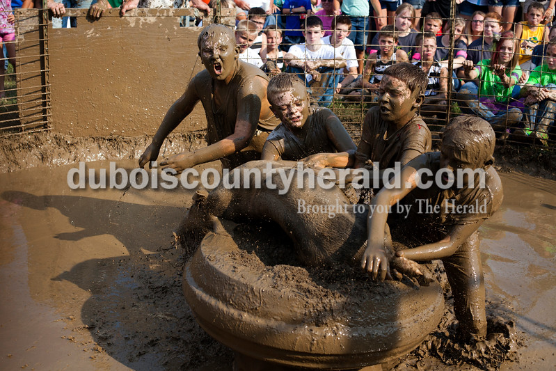 Gabe Morrison, 12, left, Dawson Vaal, 11, Bryan Farina, 11, and Blake Schaefer, 11, all of St. Meinrad, put their pig on the tire during the hog wrestling competition at the Dale Fall Fest on Saturday. Ariana van den Akker/The Herald