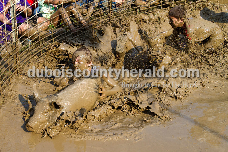 Blake Schaefer, left, tried to jump onto the pig, while his teammate Bryan Farina, both of St. Meinrad and 11, ran after them during the hog wrestling competition at the Dale Fall Fest on Saturday. Ariana van den Akker/The Herald