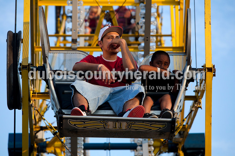 Gabriel Miranda of Jasper, left, and Emanuel Barco of Tennyson, 4, waited as people got off the ferris wheel at the Dale Fall Fest on Saturday. Ariana van den Akker/The Herald