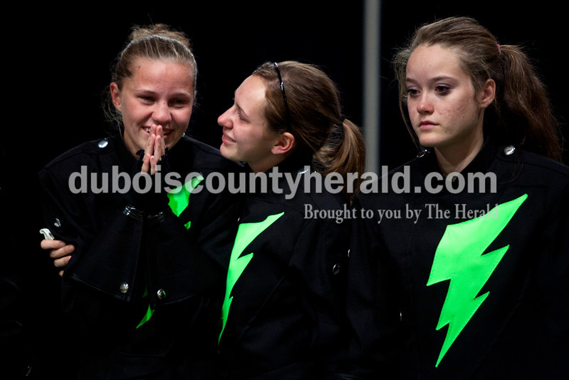 Forest Park senior Brandi Kordes, left, got a hug from junior Olivia Voegerl and senior Chelsea Englert gathered her thoughts before the Indiana State School Music Association state marching band finals at Lucas Oil Stadium in Indianapolis on Saturday.  The Rangers were awarded first place in Class D for the second year in a row.  Ariana van den Akker/The Herald