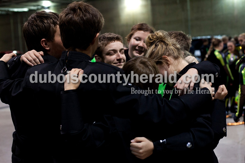 Forest Park freshman Isaac Herndon and senior Elizabeth Fleck joined in a group hug with the rest of the drum line while waiting to practice before the Indiana State School Music Association state marching band finals at Lucas Oil Stadium in Indianapolis on Saturday.  The Rangers were awarded first place in Class D for the second year in a row.  Ariana van den Akker/The Herald