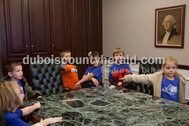 Rachel Mummey/The Herald<br /> Holy Family kindergarteners Tatum Wehr, left, Aiden Persohn, Nicholas Kieffner, Kate Veleeparmbil, Jonah Kuczynski, Gracie Huckelby took guesses on which chair belonged to Mayor Terry Seitz in the conference room at Jasper City Hall during their Mystery Minute Field Trip on Friday. The group received a tour of City Hall, met Mayor Terry Seitz and sang Christmas songs to city employees.