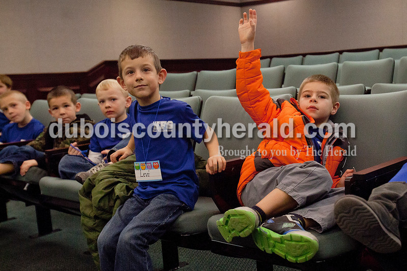 Rachel Mummey/The Herald<br /> Holy Family kindergartener Nicholas Kieffner, right, rose his hand with a question with his classmates Levi Clauss, second from right,  Alec Wehr, Aiden Persohn and Nate Weinzapfel, at Jasper City Hall during their Mystery Minute Field Trip on Friday. The group received a tour of City Hall, met Mayor Terry Seitz and sang Christmas songs to city employees.