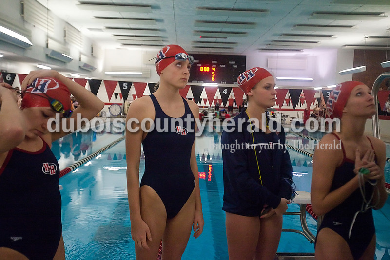 Heritage Hills girls 200 yard medley relay team Brielle Forler, Aubrey Marrs, Emma Burns and Sienna Crews look up at the flag during the National Anthem before the start of Monday night's swim meet against Southridge in Huntingburg. Rachel Mummey/The Herald