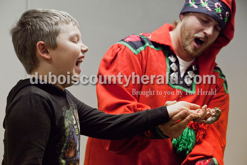 Blakely McLemore of Huntingburg, 7, left, howled with laughter as he held onto a tree frog named Jell-O with help from Candy Cane Chris from the Silly Safari's Indiana Reindeer Reserve based out of Indianapolis at the Huntingburg Public Library on Tuesday. Rachel Mummey/The Herald