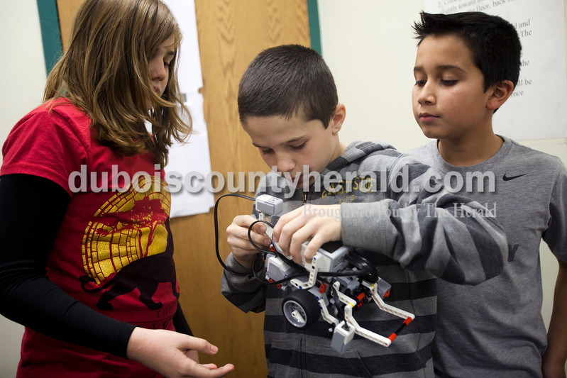 Ariana van den Akker/The Herald<br /> Lincoln Trail Elementary fifth-grader Grace Gasaway, left, and Nancy Hanks Elementary fifth-grader Erik Thomas, right, watched as Nancy Hanks Elementary sixth-grader Zach Fortune attached pieces to their robot after Grace and Erik programed it last Wednesday during a weekly robotics program for fifth and sixth graders in the North Spencer County School Corporation hosted at Heritage Hills Middle School.  During the 12-week program, students learned to build and program lego robots.