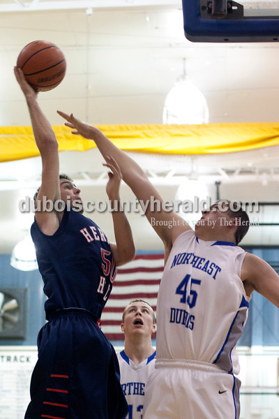 Northeast Dubois Eric Dodson tried to block a shot by Heritage Hills' Spenser Minto during Tuesday night's game in Dubois.  The Patriots won 74-54.  Ariana van den Akker/The Herald