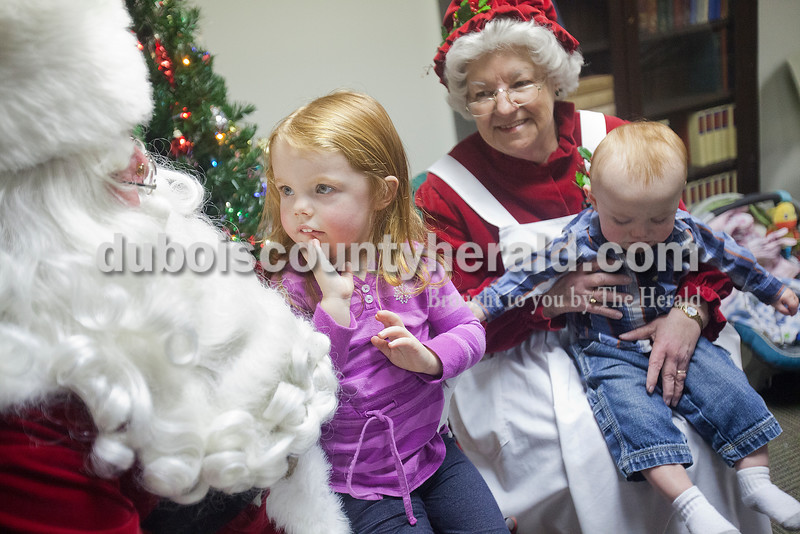 Adalyn Haefling of Dale, 3, second from left, told Santa what she wanted for Christmas while her nine-month-old brother Ian, right, sat on Mrs. Claus's lap during their visit to the Huntingburg Public Library on Tuesday. Rachel Mummey/The Herald