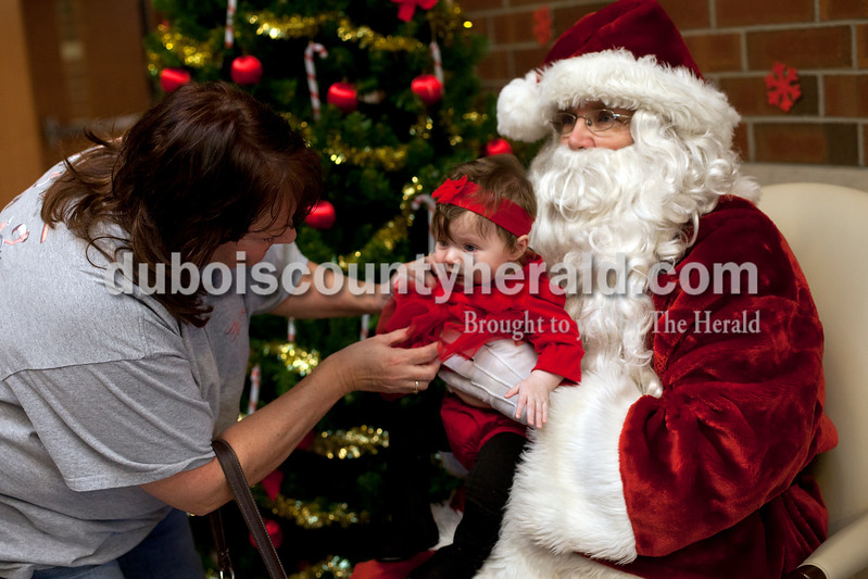 Ariana van den Akker/The Herald<br /> Sarah Kinder adjusted the dress on her granddaughter Isabelle Kinder, 3 months, both of Jasper, before they took a picture of her with Santa (Steve Schoppenhorst of Huntingburg) at the American Legion Post 147 and Auxiliary's 76th annual Christmas Party for children at Jasper Middle School on Saturday.  The Jasper Middle School band serenaded the crowd until Santa arrived and greeted everyone in the gym before visiting with the children.