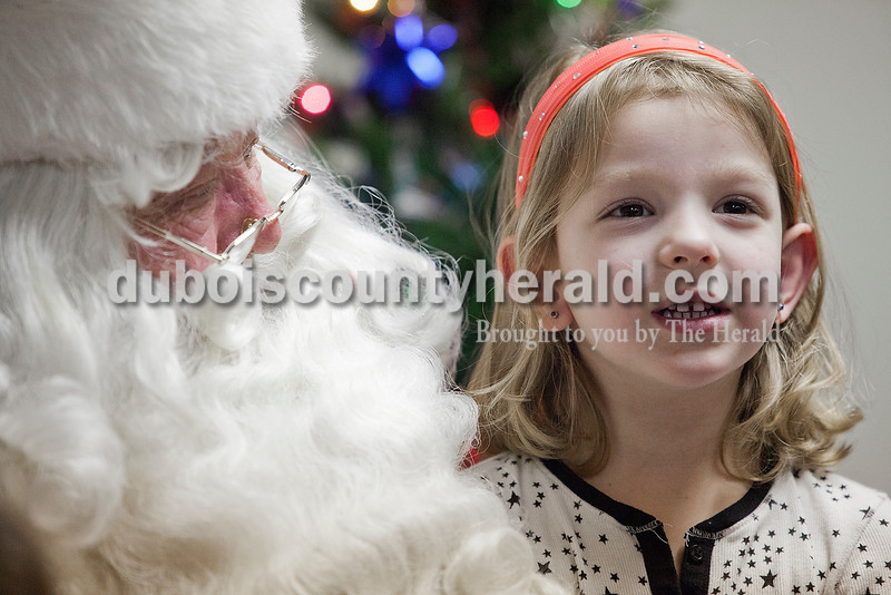 Ardyn Larson of Huntingburg, 5, right, told Santa what she wanted for Christmas during his visit to the Huntingburg Public Library on Tuesday.  Rachel Mummey/The Herald