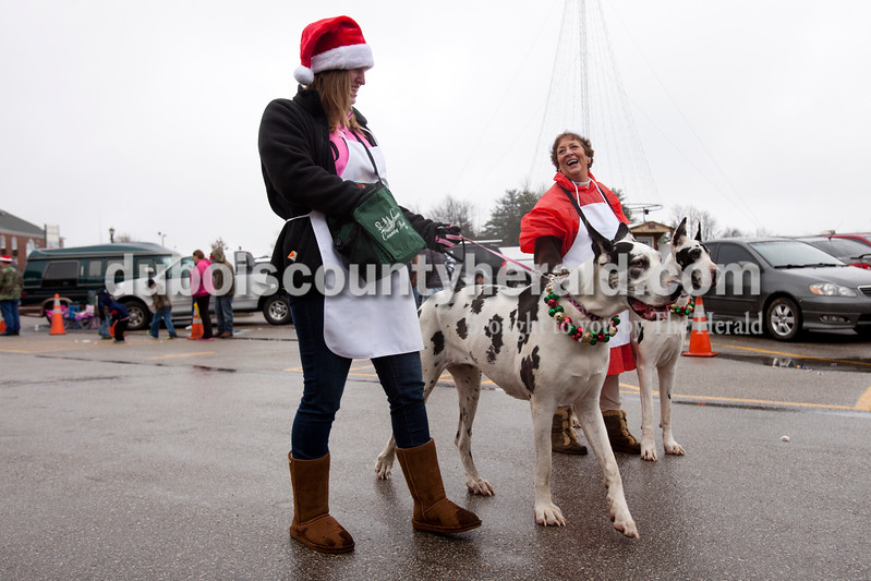 Ariana van den Akker/The Herald<br /> Crystal Boehm of New Boston, left, passed out candy as she and Nancy Underwood of Mariah Hill laughed as they tried to wrangle Nancy's two Great Danes Gamine, left, and Noelle as they walked with Spencer County Bank's float during the annual Santa Claus Christmas Celebration Parade on Saturday afternoon in Santa Claus.