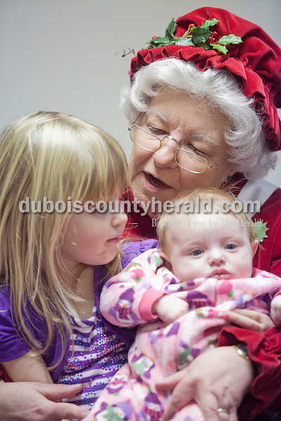 Brooke Deorto of Dale, 4, left, and her three-month-old half sister Chloe Lee, right, sat on Mrs. Claus' lap during their visit to the Huntingburg Public Library on Tuesday. Rachel Mummey/The Herald
