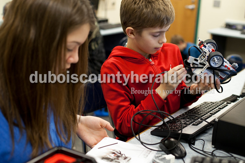 Ariana van den Akker/The Herald<br /> Nancy Hanks Elementary sixth-grader Daley Atchison, left, read a programming manual as her robotics partner Lincoln Trail Elementary fifth-grader Jacob Smith plugged in the robot to transfer programming data to it Wednesday during a weekly robotics program for fifth and sixth graders in the North Spencer County School Corporation hosted at Heritage Hills Middle School.  During the 12-week program, students learned to build and program lego robots.
