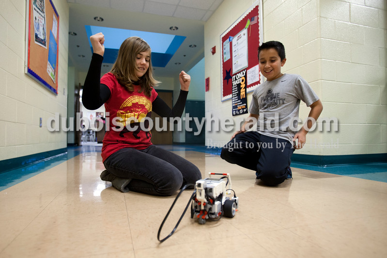 Ariana van den Akker/The Herald<br /> Lincoln Trail Elementary fifth-grader Grace Gasaway, left, raised her hands in victory and she and Nancy Hanks Elementary fifth-grader Erik Thomas watched their robot catch and drag a box just like they programmed it do do on Wednesday during a weekly robotics program for fifth and sixth graders in the North Spencer County School Corporation hosted at Heritage Hills Middle School.  During the 12-week program, students learned to build and program lego robots.