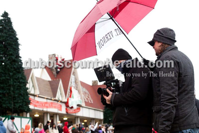 "Ariana van den Akker/The Herald<br /> Tanner Beard, right, director of a movie called ""Just Be Claus,"" held an umbrella over director of photography Philip Roy, both of Austin, Texas, as Roy filmed scenes from the annual Santa Claus Christmas Celebration Parade in Santa Claus on Saturday.  The crew was in town to film b-roll for the upcoming movie, which will be filmed in the next few months in town."