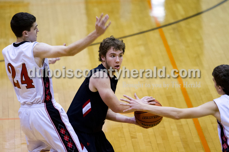 Southridge's Connor Craig passed the ball while guarded by North Posey's Jacob Brenton, left, and Drake Davenport during Saturday evening's fifth-place game at the Graber Post Buildings Classic at North Daviess High School.  Southridge won 56-41.  Ariana van den Akker/The Herald