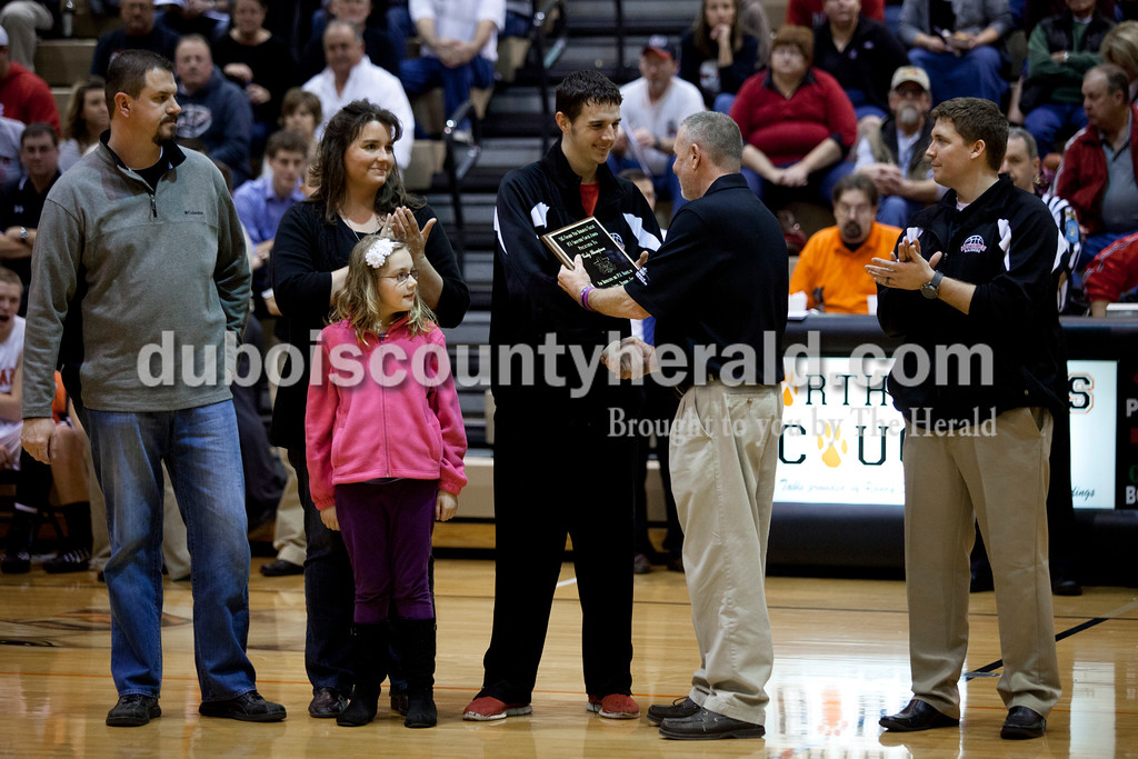 Ron Bratton, the Daviess-Martin County FCA representative, presented Southridge's Cody Thompson with FCA Character Counts award as Cody's parents Scott and Amanda Thompson of Huntingburg and his sister Ella, 7, watched along with Southridge coach Jeremy Rauch after Saturday evening's fifth-place game against North Posey at the Graber Post Buildings Classic at North Daviess High School.  Southridge won 56-41.  Each team nominated a player for the award and the FCA State Office in Fort Wayne chose Cody from those nominated.  Ariana van den Akker/The Herald